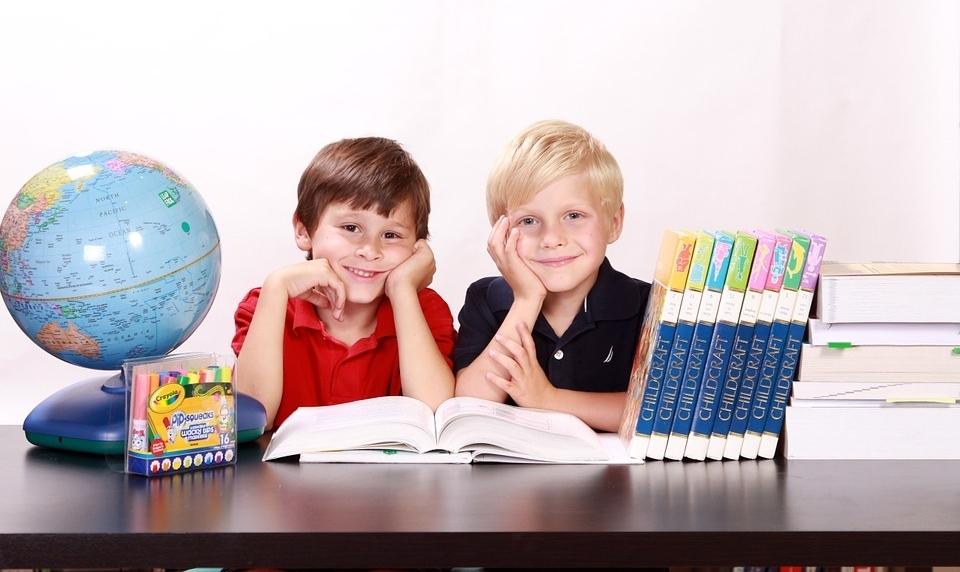 Dwoje dzieci przy stole, przed nimi rozłożone książki, obok na stole globus, a z drugiej strony stos książek.