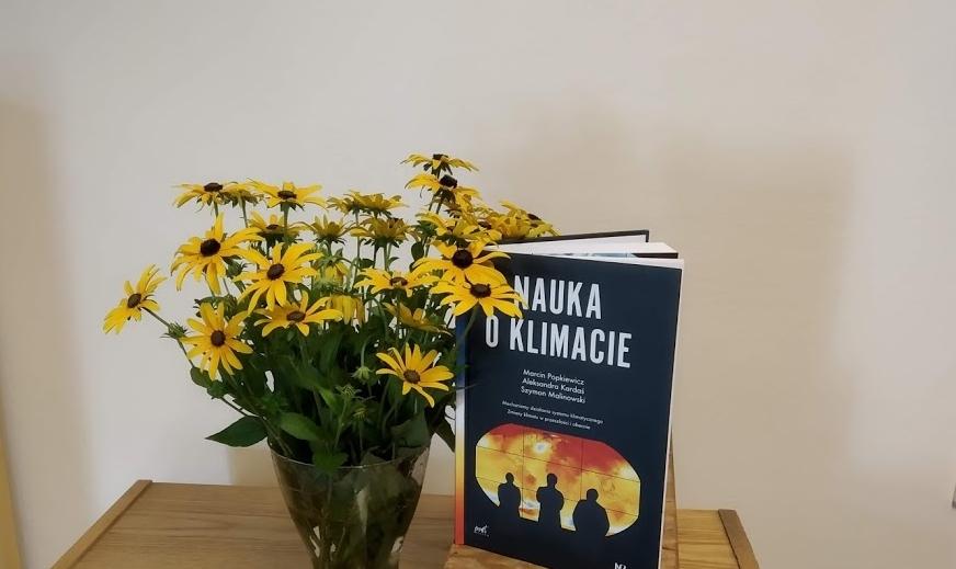 """Okładka książki """"Nauka o klimacie"""" obok wazonu z żółtymi kwiatami."""