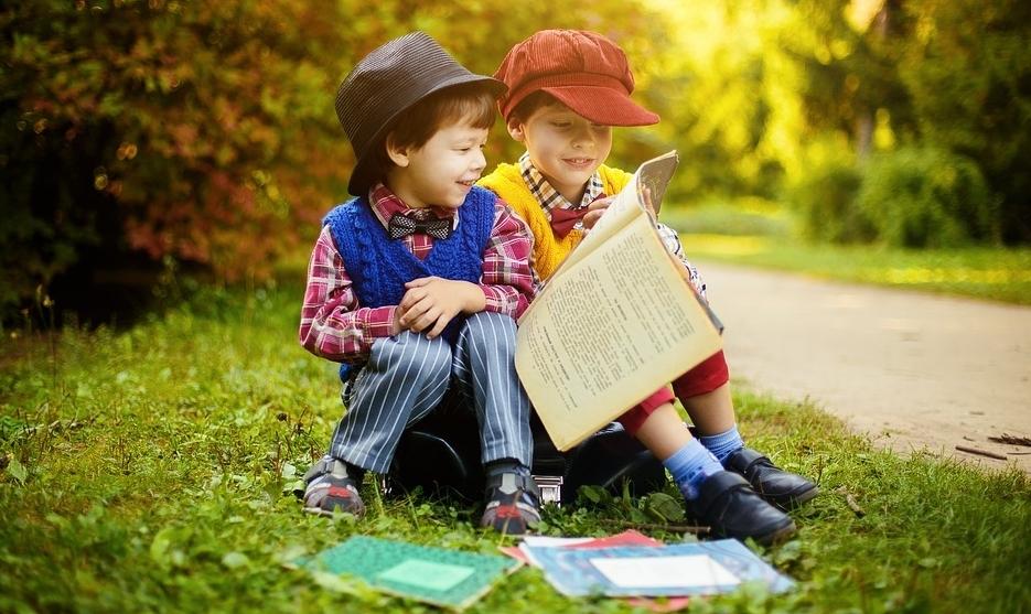 Dwójka dzieci siedzi na trawie i przegląda książki.