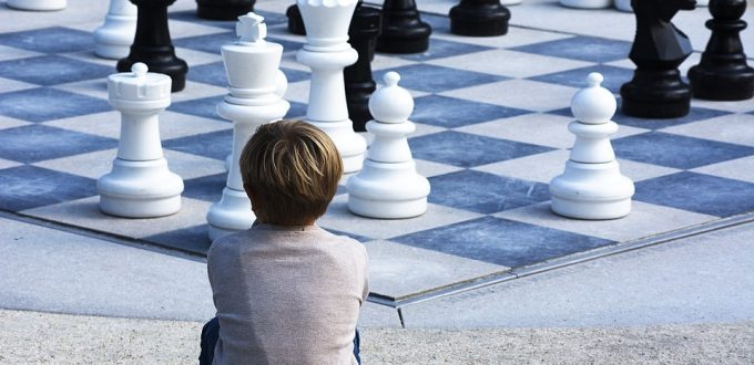 duża plansza szachowa a na niej pionki. Obok siedzi chłopiec patrzący na planszę