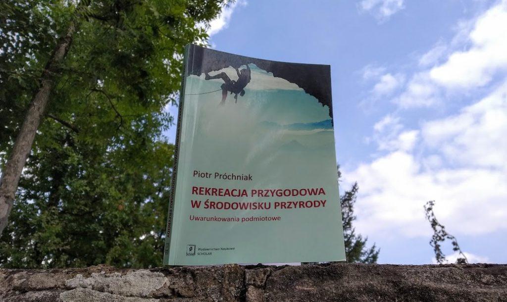 """Na tle nieba okładka książki """"Rekreacja przygodowa w środowisku przyrody""""."""