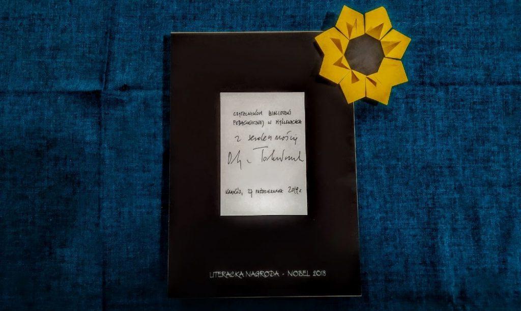 Ramka leżąca na niebieskim suknie, a w niej dedykacja i podpis Olgi Tokarczuk.