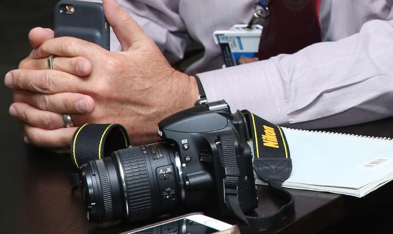 Ręce trzymające telefon komórkowy a obok leżący na stole aparat fotograficzny.