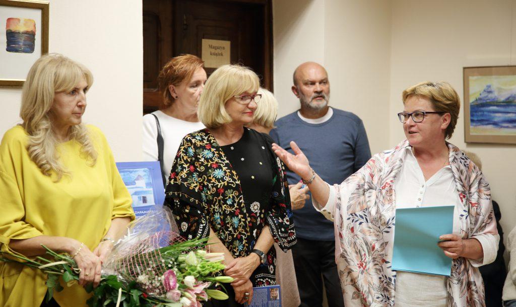 Kilka osób - uczestników wernisażu, w tym artystka Jolanta Czernecka