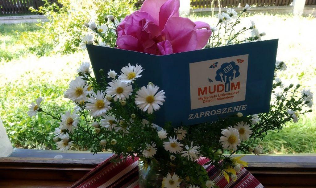 Zaproszenie na otwarcie roku akademickiego MUDiM wkomponowane w bukiet żywych kwiatów.