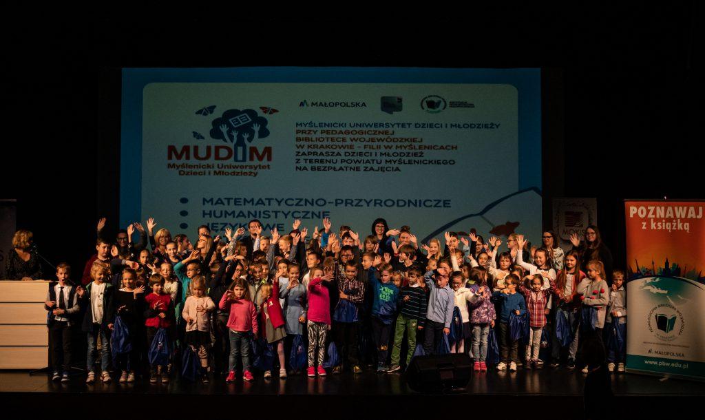 Autor Krzysztof Szymoniak Grupa dzieci- studentów, stojących na scenie,  wesoło uśmiechniętych, machających rękami. W tle plakat z logo MUDiM.