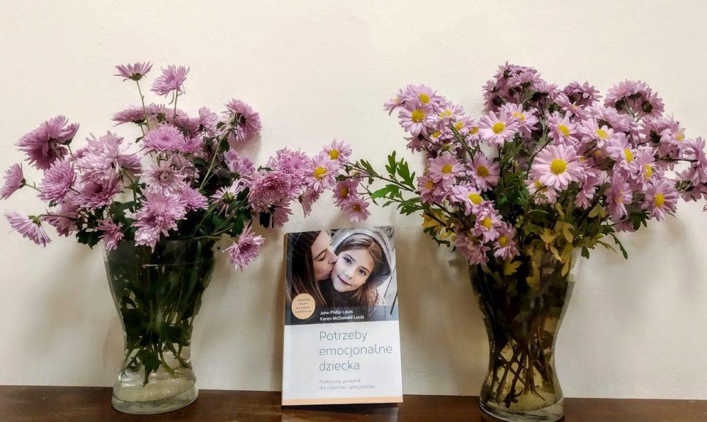 """Dwa bukiety liliowych kwiatów we flakonach, a pomiędzy nimi książka """"Potrzeby emocjonalne dziecka""""."""