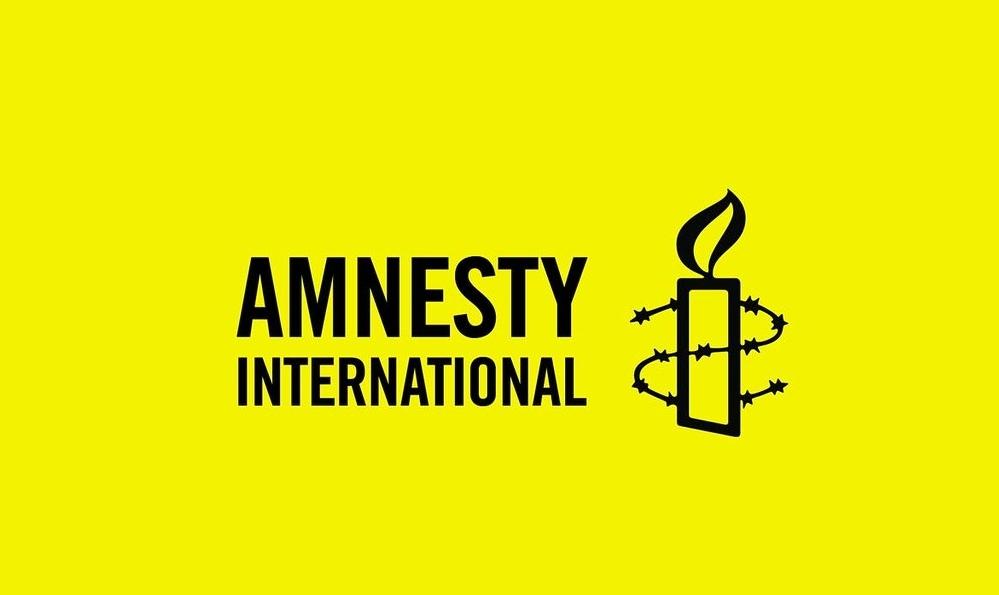 Plakat z napisem Amnesty International. Obok napisu rysunek świeczki otoczonej drutem kolczastym