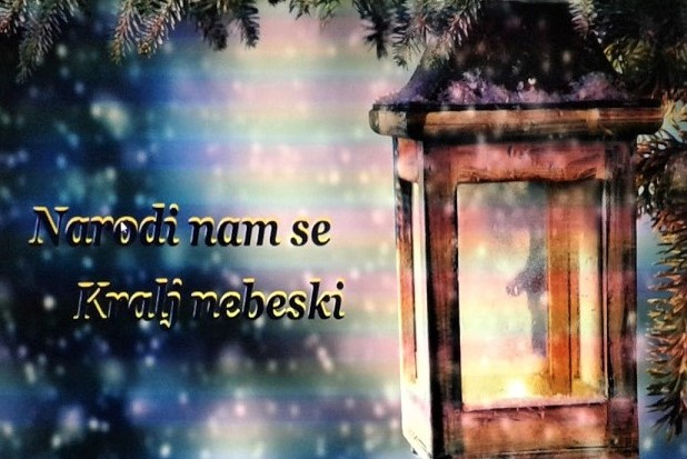 """Napis po chorwacku """"Narodi nam se Kralj nebeski"""". W tle padający śnieg. Obok napisu latarnia zawieszona na drzewie."""