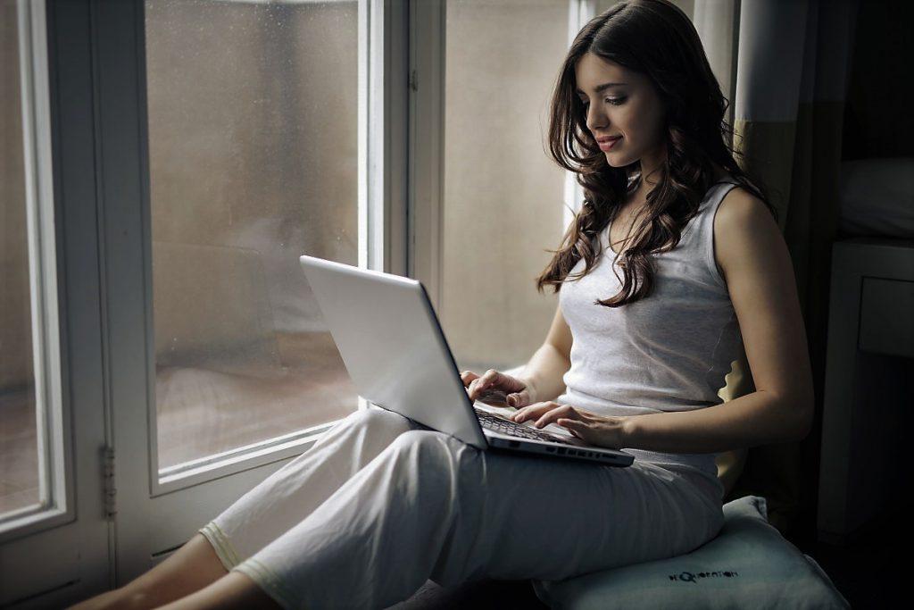 Na zdjęciu widok kobiety o długich, ciemnych, lekko pokręconych włosach. Kobieta ubrana jest w białą koszulkę na ramiączkach i białe spodnie. Siedzi na parapecie bokiem do okna, na kolanach trzyma otwarty laptop. Palce kobiety stukają w klawiaturę laptopa
