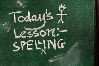 Zielona tablica szkolna, a na niej kredą napisane Todays Lesson - Spelling. Z Prawej strony narysowany kredą ludzik.