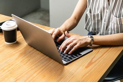Fragment blatu stolika, na którym stoi laptop i kubek. Przy stoliku kobieta pracuje na laptopie. Widać tylko jej ręce i fragment tułowia