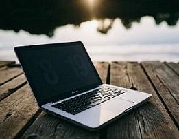 Na zdjęciu otwarty laptop na drewnianym pomoście. Na ekranie laptopa wyświetla się godzina 8:19. W tle tafla wody i skrawek zachodzącego slońca