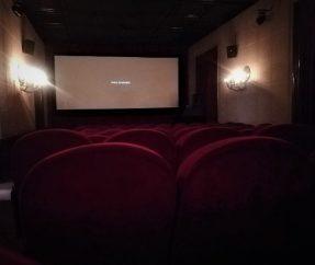 widok małej sali kinowej. Sfotografowane od tyłu filmowe fotele. W oddali biały ekran. Z boku, na ścianach świecące słabym światłem lampy.