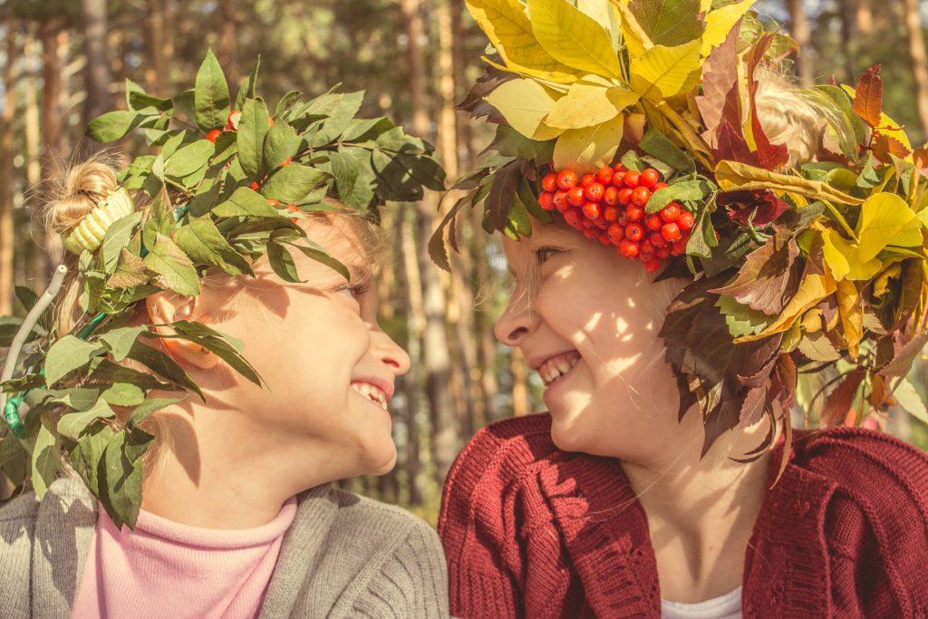 Zdjęcie dwójki uśmiechniętych dzieci zwróconych do siebie twarzami. Dzieci mają na głowach kolorowe wianki zrobione z roślin.