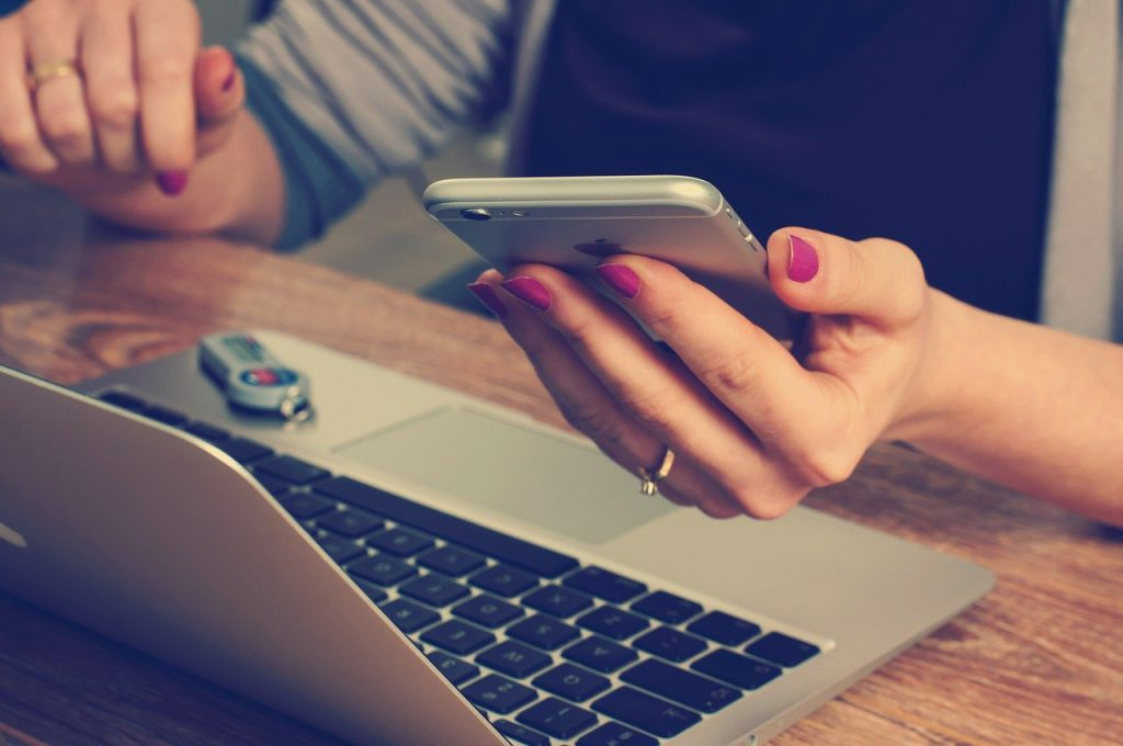 na brązowym blacie leży laptop w kolorze szarym, przed laptopem widać kobiece ręce. W jednej dłoni kobieta trzyma telefon komórkowy