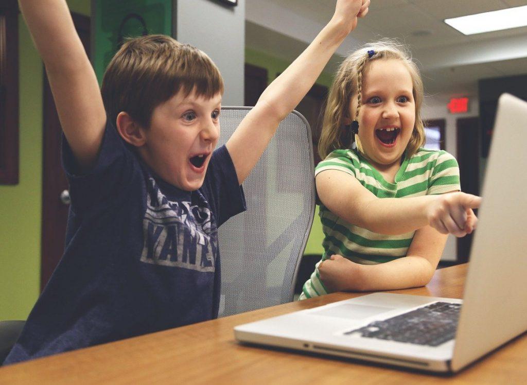 Dzieci- chłopiec i dziewczynka uśmiechnięci, radośni wpatrzeni w ekran laptopa, który stoi przed nimi. Chłopiec unosi ręce w górę, dziewczynka pokazuje palcem na ekran