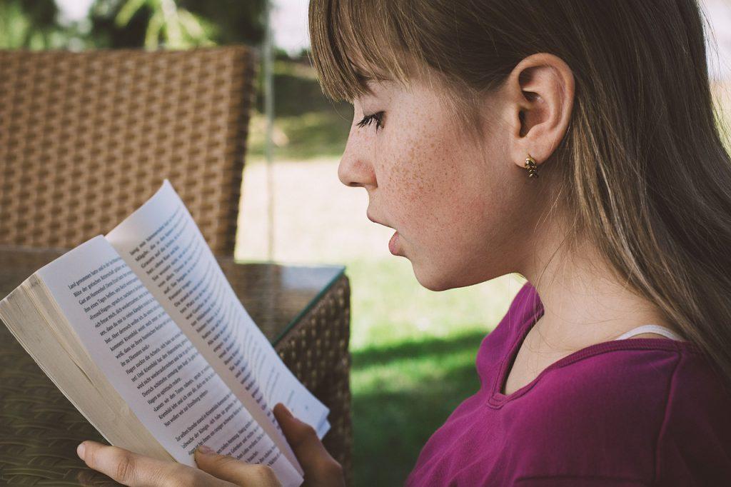 Dziewczynka z długimi włosami w fioletowej bluzce, ukazana z profilu czyta książkę.